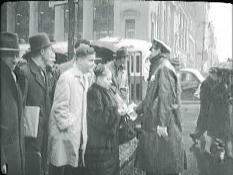 vídeos de stock, filmes e b-roll de montage policeman directing pedestrians across city street on a rainy day / los angeles, california, united states - capa de chuva