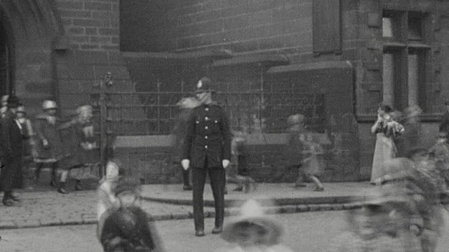 1925 montage policeman directing students and vehicle traffic in after school rush, with students crossing busy street, policeman stopping tram, horse drawn wagon, and bicyclist / newcastle upon tyne, england, united kingdom - cart stock videos & royalty-free footage