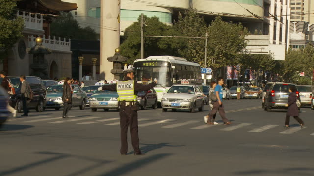 policeman directing traffic in shanghai china - directing stock videos and b-roll footage