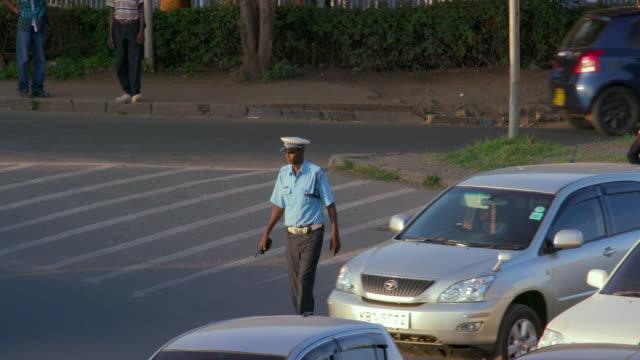policeman directs traffic at mombasa rd roundabout nairobi  kenya  africa - zambia stock videos & royalty-free footage
