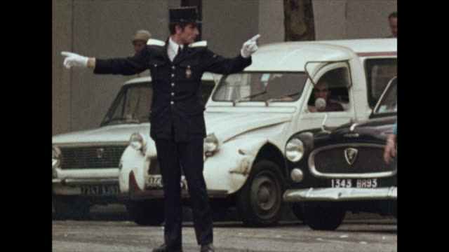 policeman directs traffic in the middle of paris street, 1972 - french culture stock videos & royalty-free footage
