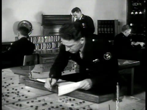 policeman dispatcher handing paper to officer working desk manhattan map w/ police car positions marked w/ numbered discs. night: black and white'... - 1939 stock-videos und b-roll-filmmaterial