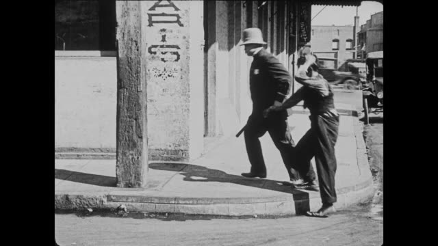 1920 Policeman (Eddie Cline) escorts paint soaked man (Buster Keaton) straight into a lamppost before taking him to jail