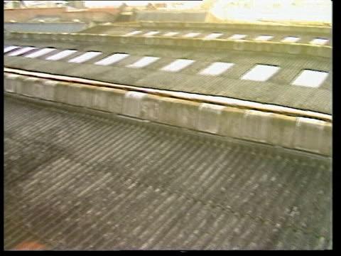east london gv pan warehouse ts pan roof zoom in pc's radio dropped in chase cs broken roof light tilt spot where pc fell lms interior warehouse cas... - イーストロンドン点の映像素材/bロール