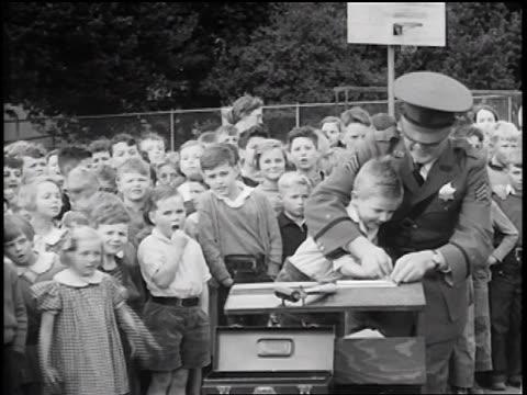 B/W 1936 policeman fingerprinting little boy at table / crowd of children in background / newsreel