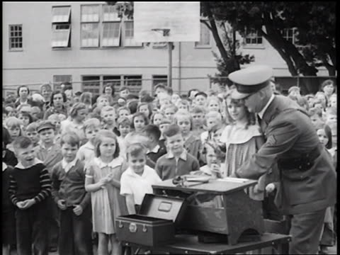 vidéos et rushes de b/w 1936 policeman fingerprinting little girl at table / crowd of children in background / newsreel - âges mélangés