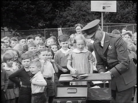 b/w 1936 policeman fingerprinting little girl at table / crowd of children in background / newsreel - newsreel stock videos & royalty-free footage