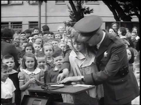 vidéos et rushes de b/w 1936 policeman fingerprinting little girl at table outdoors / crowd of children in background / newsreel - âges mélangés