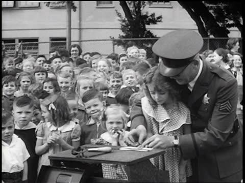 stockvideo's en b-roll-footage met b/w 1936 policeman fingerprinting little girl + setting her down / crowd of children in background / news. - gemengde leeftijdscategorie