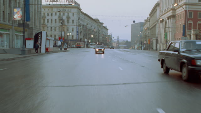 a policeman follows traffic along a city street in moscow. - russia stock-videos und b-roll-filmmaterial