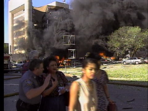 policeman guides three dazed survivors away from the bombed oklahoma city federal building. - oklahoma city bombing stock videos & royalty-free footage