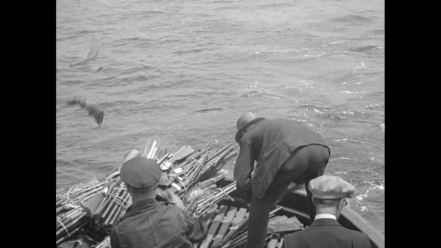 policeman handing man on boat at dock armloads of shotguns, rifles and machine guns, man dumps the guns on boat deck / another man dumps armful of... - rifle stock videos & royalty-free footage