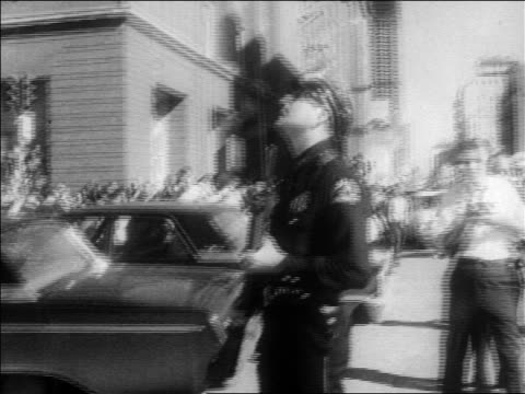 b/w 1963 policeman holding gun looking up outdoors / kennedy assassination / dallas - attentat auf john f. kennedy stock-videos und b-roll-filmmaterial