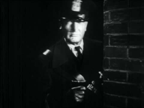 b/w 1934 policeman holding pistol turning head by corner of building at night - 少於10秒 個影片檔及 b 捲影像