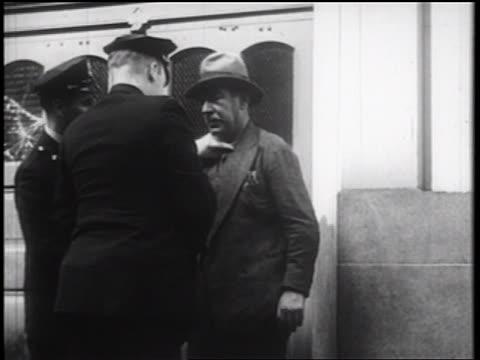 B/W 1939 policeman holding up drunk man on city sidewalk / NYC / documentary