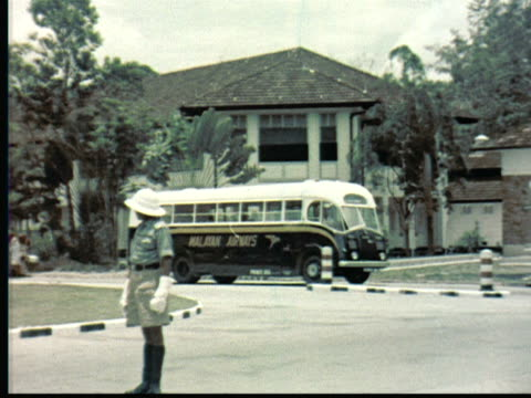 1957 MONTAGE Policeman in shorts directs traffic using hand signals. Malayan Airways bus drives by / Singapore / AUDIO