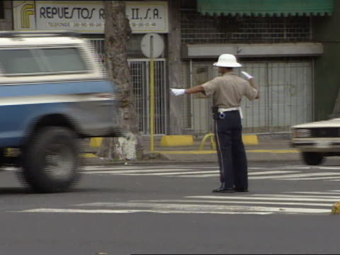 policeman in uniform, wearing white pith helmet & gloves, standing in center of street directing, regulating traffic. - directing stock videos & royalty-free footage