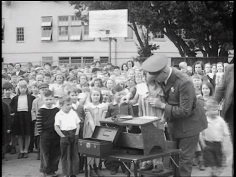 stockvideo's en b-roll-footage met b/w 1936 policeman lifting little girl to table for fingerprinting / crowd of children in background / news. - gemengde leeftijdscategorie