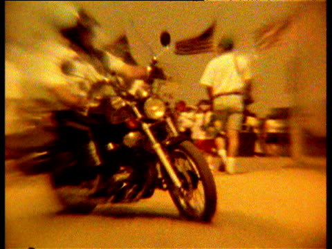 vidéos et rushes de us policeman on motorbike drives past stars and stripes flags around washington monument, yellow filter - police force