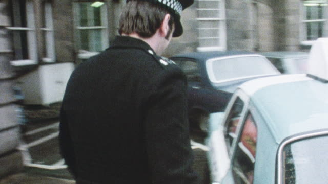 1981 montage policeman parking his car, taking an alcoholic from it, and putting him in a wheelchair at a detoxification facility / united kingdom - 1981 stock videos & royalty-free footage
