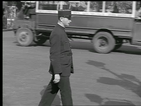 B/W 1936 PAN policeman signaling traffic to keep moving then signaling to stop / Paris, France