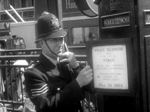 a policeman smiles at the camera while using a police telephone box 1953 - 電話ボックス点の映像素材/bロール
