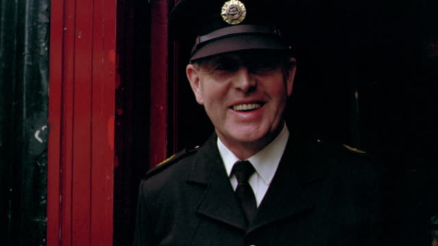 portrait policeman smiling next to red doorway / dublin, ireland - アイルランド共和国点の映像素材/bロール