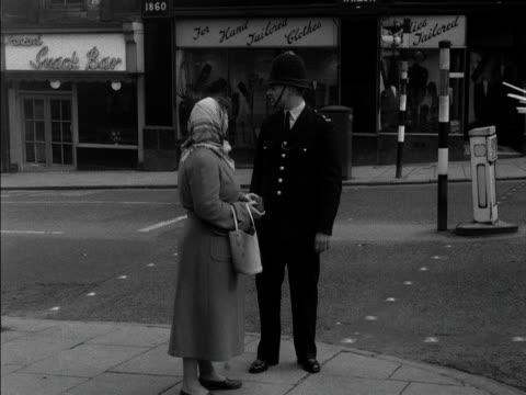 vídeos de stock e filmes b-roll de policeman speaks to a woman on a busy high street. 1957. - enfeites para a cabeça