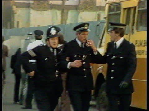 Policeman staggering towards camera supported by two colleagues Brixton Riots 11 Apr 81
