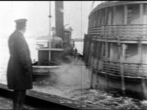 policeman standing on dock tugboat escorting doubledecker boat into harbor ws police officers man in bowler hat waving from dock - deportation stock videos and b-roll footage
