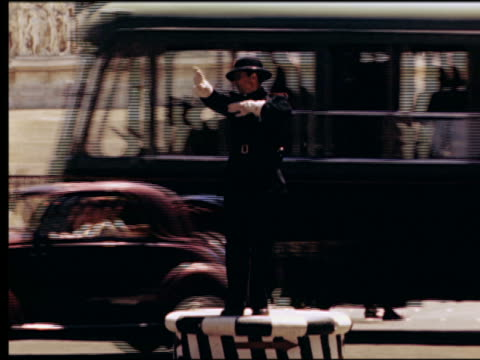 1949 policeman standing on platform directing traffic with bus on city street / rome, italy - rome italy stock videos & royalty-free footage
