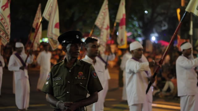 ms policeman stands guard as flag bearers parade in buddhist festival or procession 'esala perahera' (festival of tooth) audio / kandy, central province, sri lanka - sri lankan culture stock videos and b-roll footage