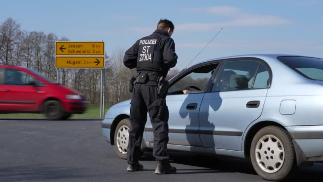 policeman talks to a car driver at a checkpoint on a road leading to the quarantined towns of schweinitz and jessen on march 26, 2020 near jessen,... - police force stock-videos und b-roll-filmmaterial