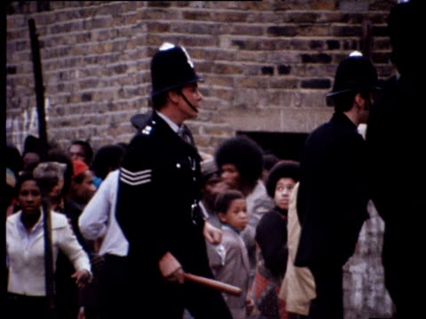 vídeos de stock e filmes b-roll de policeman threatens woman with truncheon then pushes her back during disturbances at notting hill carnival london aug 76 - notting hill