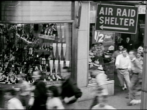 Policeman w/ whistleMan barber leave shop People running sidewalk Air Raid Shelter sign above TD Running legs items dropping curbside VS People...