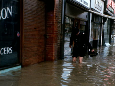 A policeman wades through flood water