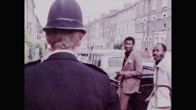 policeman walks past people leaning on car talking in brixton; 1973 - moving past stock videos & royalty-free footage