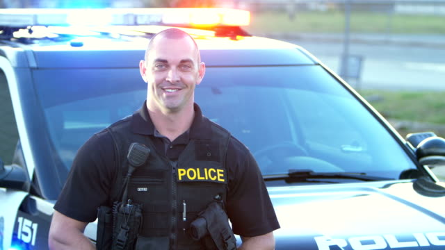 policeman wearing bulletproof vest, by patrol car - officer stock videos & royalty-free footage