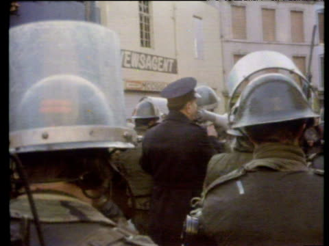 policeman with loud hailer attempts to address protestors gathered at william street army roadblock as missiles are thrown at him during civil rights... - nordirland stock-videos und b-roll-filmmaterial