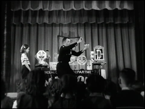 vídeos de stock, filmes e b-roll de a policeman/magician performs magic tricks while a very happy audience of 6 year olds laughs montage magic show at grade school on january 01 1954 in... - mágico