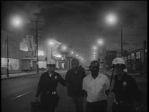 B/W 1965 policemen arresting 2 Black men on street in Watts race riots / Los Angeles / newsreel