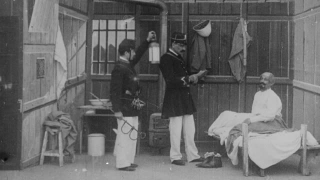 vídeos de stock e filmes b-roll de 1899 ws policemen arresting and securing prisoner to bed - cama de campanha