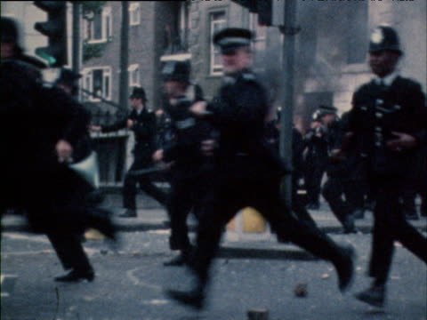 vídeos de stock e filmes b-roll de policemen charge through street past burning car carrying truncheons traffic cones and dustbin lids for protection as objects rain down during... - notting hill
