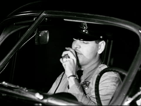 dramatization policemen in car answering radio dispatch firemen holding fire hose fireman climbing into smoking window people gathered to watch - syracuse stock videos & royalty-free footage