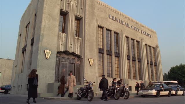 vídeos de stock, filmes e b-roll de ws policemen, people and vehicle traffic at 'central city police department' building - escrita ocidental