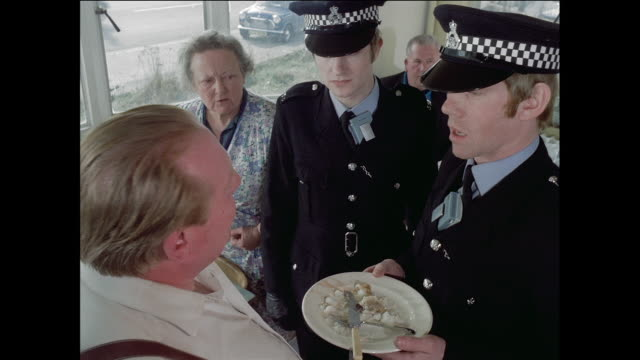 vídeos de stock, filmes e b-roll de montage policemen settling argument in restaurant & leaving for work on bicycle / london, england, united kingdom - 1973