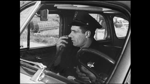 policemen sitting inside parked car, one talks to the radio then drives away - 1940 1949 stock videos & royalty-free footage