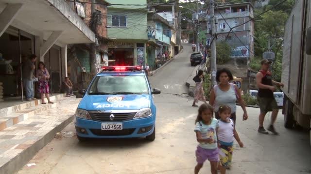 Policemen standing in front of their patrol car in Vidigal Favela Rio De Janeiro