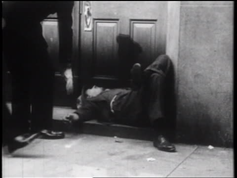 B/W 1939 policemen waking up homeless man asleep in doorway / NYC / documentary