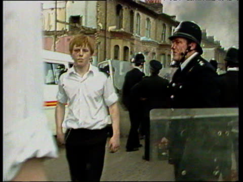 policemen with bloody faces retreat behind police lines as burning vehicles smolder in background during rioting in brixton london; apr 81 - 1981 stock videos & royalty-free footage